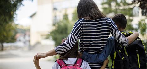 Mom walking kids to school.