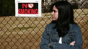 Female teen looking away by fence with no smoking sign.