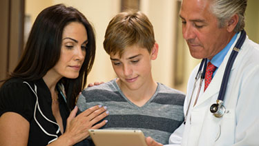 Mother, teen, and doctor talking using tablet.