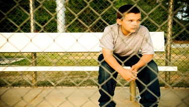 Boy alone by a fence