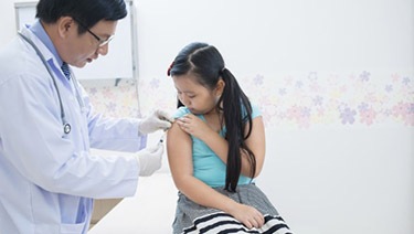 Doctor giving a flu vaccine to a young girl in his office.