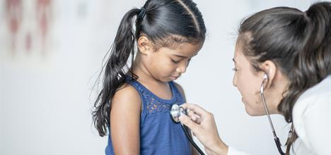 Young girl being examined by doctor.