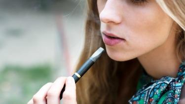 Teen girl using an e-cigarette.